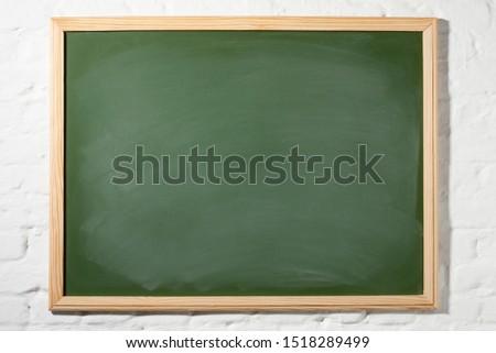 green blackboard with wood border on white brick wall #1518289499