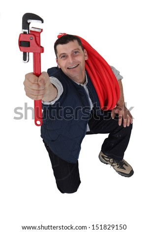 Tradesman holding up a pipe wrench #151829150