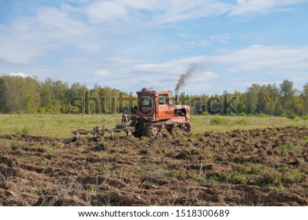 A tracked tractor with a plough plows the ground in autumn against the background of the forest. #1518300689