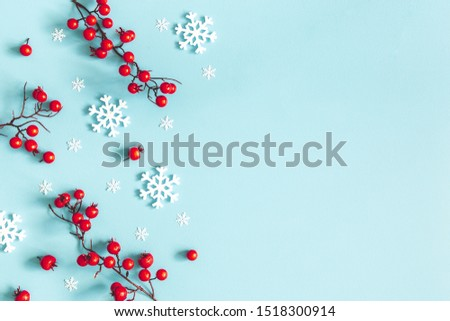 Christmas or winter composition. Snowflakes and red berries on blue background. Christmas, winter, new year concept. Flat lay, top view, copy space #1518300914