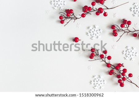 Christmas or winter composition. Snowflakes and red berries on gray background. Christmas, winter, new year concept. Flat lay, top view, copy space #1518300962
