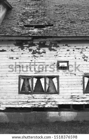 A vertical image of an old farm building sitting in disrepair. #1518376598