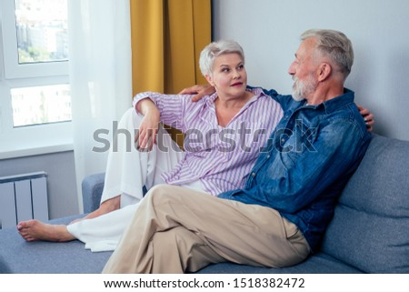 Mature good-looking well dressed couple sitting in sofa in day light from big window and yellow curtains in living room,touching hand . #1518382472