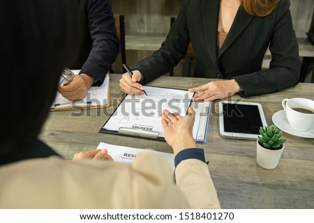 Close up view of job interview in office, focus on resume writing tips, employer reviewing good cv of prepared skilled applicant, recruiter considering application, hr manager making hiring decision. #1518401270