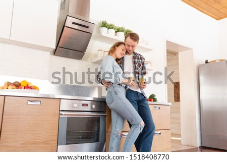 Young happy married couple in love drinking smoothie in the kitchen during the morning breakfast. Concept of energy charge and proper nutrition #1518408770