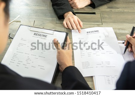 Close up view of job interview in office, focus on resume writing tips, employer reviewing good cv of prepared skilled applicant, recruiter considering application, hr manager making hiring decision. #1518410417