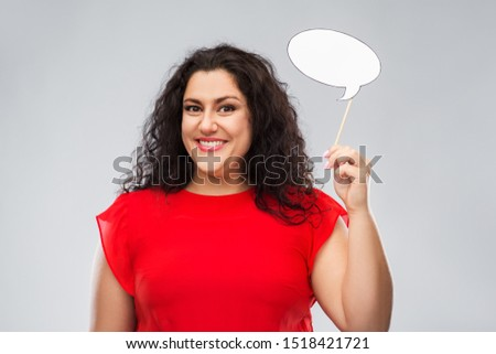 party props, photo booth and communication concept - happy woman in red dress holding big blank speech bubble over grey background