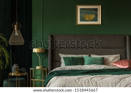 Stylish emerald green and golden poster above comfortable king size bed with headboard and pillows in dark green bedroom #1518445667