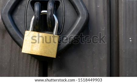 Close up of a chrome and gold textured padlock locking a plastic outside storage unit. Image taken on an overcast day. #1518449903
