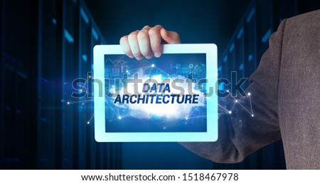 Young business person working on tablet and shows the inscription: DATA ARCHITECTURE #1518467978