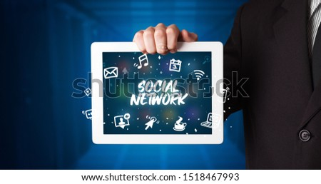 Young business person working on tablet and shows the inscription: SOCIAL NETWORK #1518467993