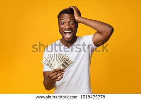 Excited Afro Guy Holding Money Shouting Touching Head Standing On Yellow Studio Background. Big Luck. Free Space #1518475778