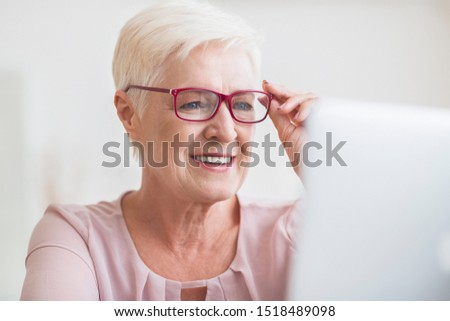 Vision problem concept. Attractive senior business lady sitting in front of laptop, enjoying her new stylish glasses, close up, copy space #1518489098