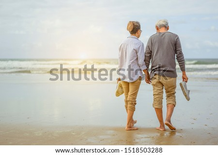 Senior couple walking on the beach holding hands at sunrise, plan life insurance at retirement concept. #1518503288