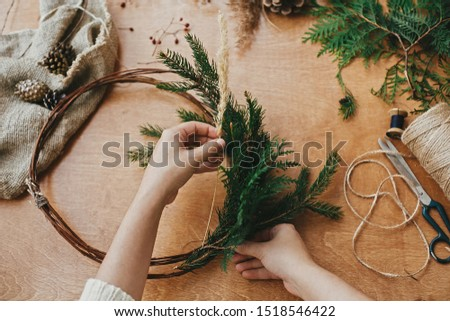 Hands holding herbs, fir branches, pine cones, berries, thread, scissors on wooden table. Making rustic christmas wreath. Christmas wreath workshop. Authentic rural wreath #1518546422