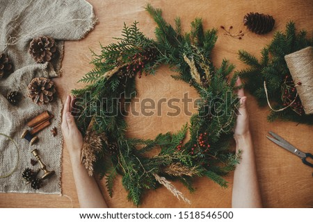 Rustic Christmas wreath, flat lay. Hands holding christmas wreath with fir branches, berries, pine cones, and thread, scissors on rural wooden table. Christmas wreath workshop #1518546500