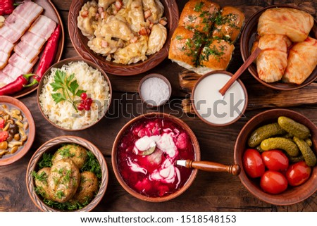 Traditional Ukrainian dishes in clay pots - borsch with sour cream, baked potatoes, garlic pampushki, sauerkraut, lard, canned tomatoes and cucumbers, mushrooms. Royalty-Free Stock Photo #1518548153
