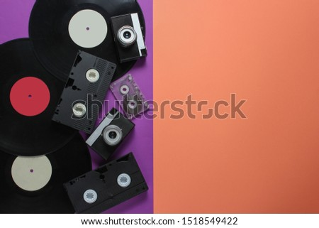 Retro objects. Retro camera, vinyl records, video cassettes, audio cassette on a colored background with copy space. 80s. Top view #1518549422