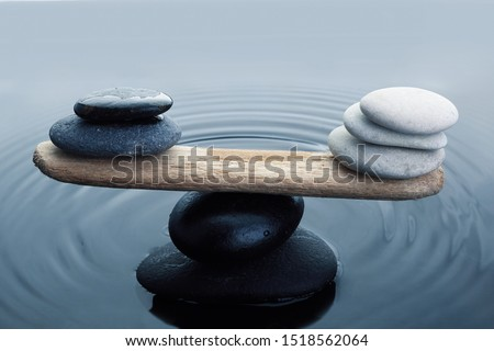 Carefully balanced black and white stones in water