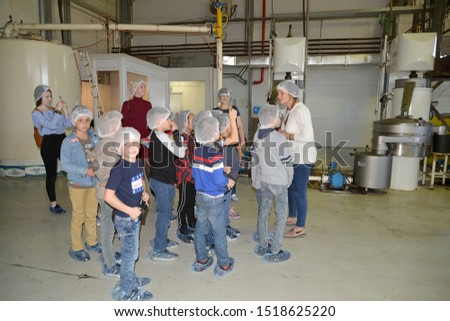 KALININGRAD, RUSSIA - SEPTEMBER 27, 2019: Children listen to a tour guide in a production shop. Children s tour to the chocolate factory BELGOSTAR #1518625220