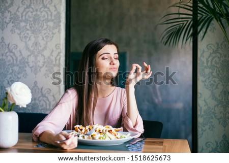 Pretty young lady sitting in a beautiful restaurant, enjoying lunch or dinner and making delicious hand gesture to express how good the food is.  Royalty-Free Stock Photo #1518625673
