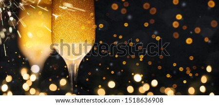 Two glasses of champagne with golden confetti, glitter, serpentine and lights. #1518636908