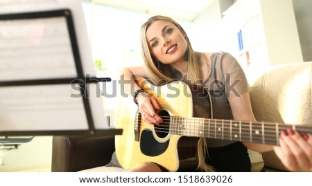 Guitar Playing Lesson Pretty Woman Hold Instrument. Smiling Lady with Musical Instrument. Blond Caucasian Girl Enjoy Music at Home Alone. Notes Stand on Music Rack. Fun Hobby Concept #1518639026