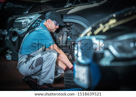 Caucasian Car Mechanic and His Automotive Job. Auto Service Shop. Servicing Modern Vehicle Brakes.  #1518639521