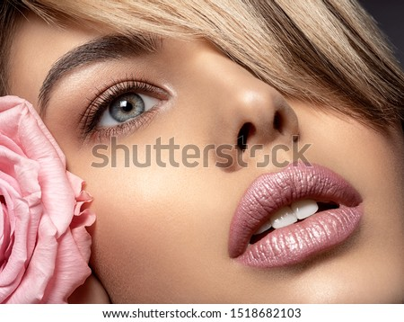 Beautiful young fashion woman with red lipstick. Glamour fashion model with bright gloss make-up  posing at studio. CLoseup beauty portrait with a flower. light pink rose. #1518682103
