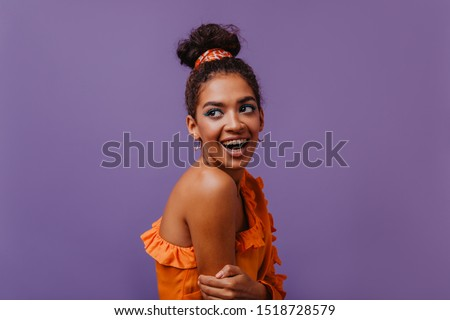 Lovely laughing woman with brown skin posing in orange dress. Joyful african girl with short hair standing on purple background. #1518728579