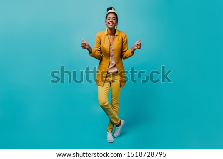 Positive african woman in trendy yellow costume smiling to camera. Indoor photo of pretty black girl standing on blue background. #1518728795