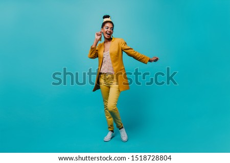 Full-length portrait of jocund black woman with casual hairstyle. Joyful african girl dancing on blue background. #1518728804