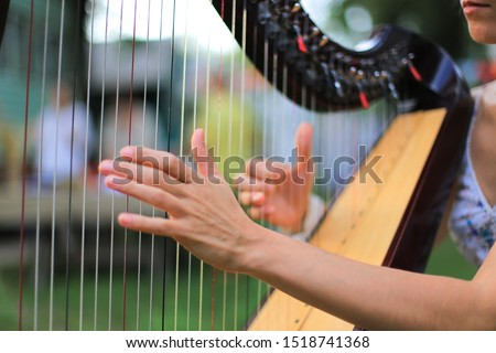 Woman playing the harp close up. Fingers playing the strings of a harp. Royalty-Free Stock Photo #1518741368