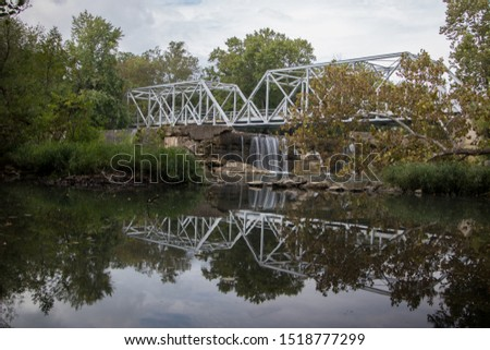 Old iron bridge over the Finley River in Ozark Missouri. Small water fall with beautiful reflection of bridge. #1518777299