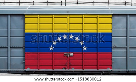 Front view of a container train freight car with a large metal lock with the national flag of Venezuela.The concept of export-import,transportation, national delivery of goods and rail transportation #1518830012