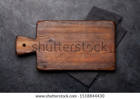 Cutting board over towel on stone kitchen table. Top view flat lay Royalty-Free Stock Photo #1518844430