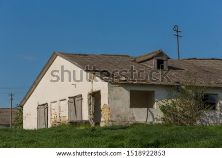 Old abandoned farm building stands alone on edge of green grass against the vast blue sky #1518922853