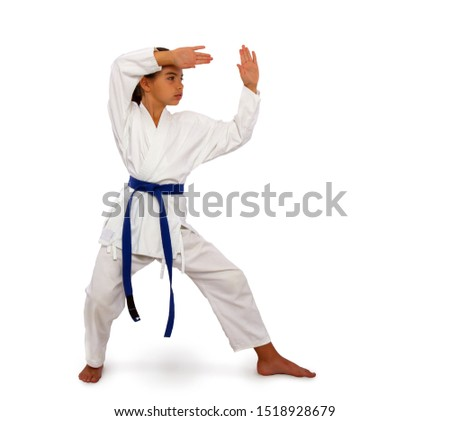 a karate girl in a white kimono and a blue belt performs an exercise from kata in training Royalty-Free Stock Photo #1518928679