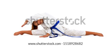 little karate girl in a white kimono and a blue belt sits for a workout in sports twine #1518928682