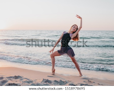 Dancing ballerina in black silk dress on embankment near ocean or sea at sunrise or sunset. Silhouette of young woman with long hair practicing classic exercises with emotions #1518978695