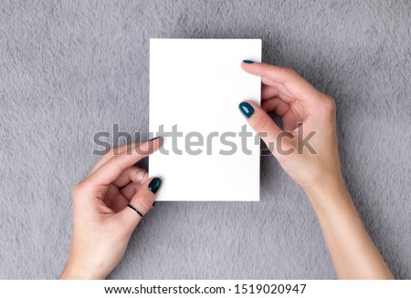 Manicured woman's hands holding postcard on grey furry background. Plain call-card mock up template.