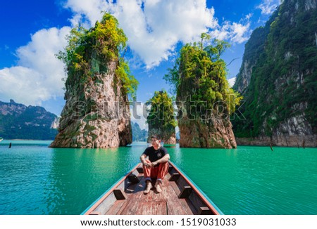 SURATTHANI,THAILAND-JULY 14,2019:Tourists ride on a boat to admire the natural beauty of Ratchaprapa Dam and Cheow Lan Lake, Khao Sok Sub-district, Surat Thani Province, Thailand #1519031033