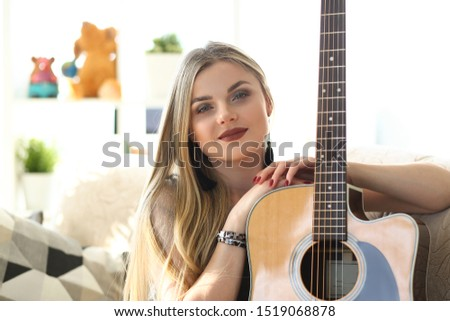 Female Guitar Player Musical Performer Portrait. Attractive Caucasian Woman Holding Instrument. Young Composer Sit on Couch Head and Shoulders Front Shot. Beautiful Musician Girl Looking at Camera #1519068878