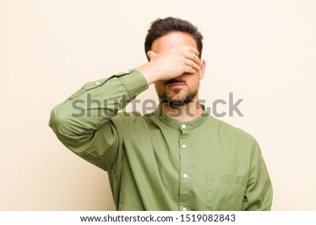 young handsome man covering eyes with one hand feeling scared or anxious, wondering or blindly waiting for a surprise #1519082843