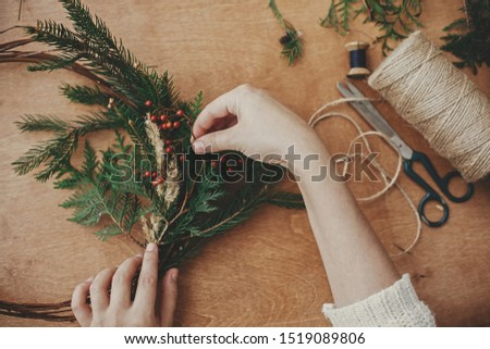 Christmas wreath workshop. Hands holding fir branches, pine cones, berries, thread, scissors on wooden table, flat lay. Making rustic christmas wreath. Authentic rural wreath #1519089806