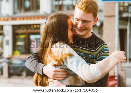 A red-haired young man embraces a young woman with long dark hair, they laugh and fool around, standing on a bridge in the center of the city. Concept of first teenage love, relationship, love  #1519104356