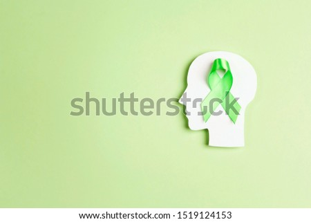 World mental health day concept. Green awareness ribbon with brain symbol on a green background. Copy space for text. #1519124153