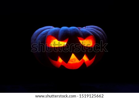 Close up image of one halloween pumpkin with burning mouths on empty black background