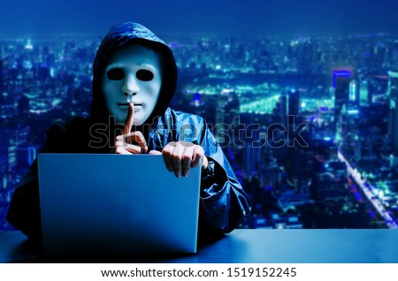 Anonymous computer hacker in white mask and hoodie. Obscured dark face making silence gesture on modern city background, Data thief, internet attack, darknet and cyber security concept.