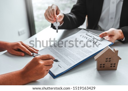 Sale Agent giving house keys to woman customer and sign agreement documents for realty purchase. #1519163429